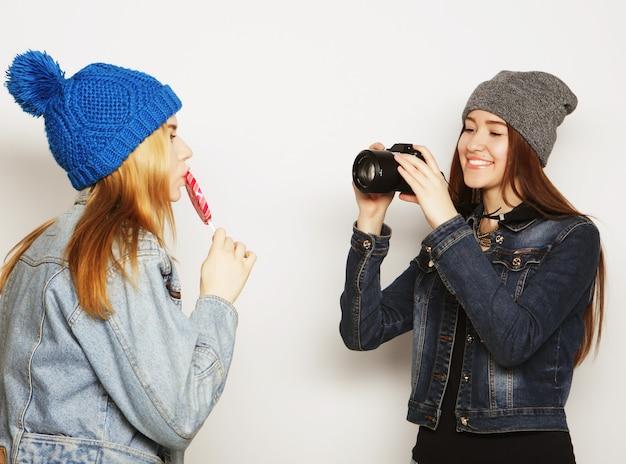Una ragazza fa una foto alla sua amica davanti su uno sfondo bianco white