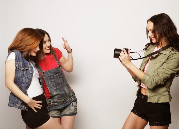 Una ragazza fotografa i suoi amici. concetto di amicizia e divertimento. migliori amici che si godono il momento con la fotocamera moderna.