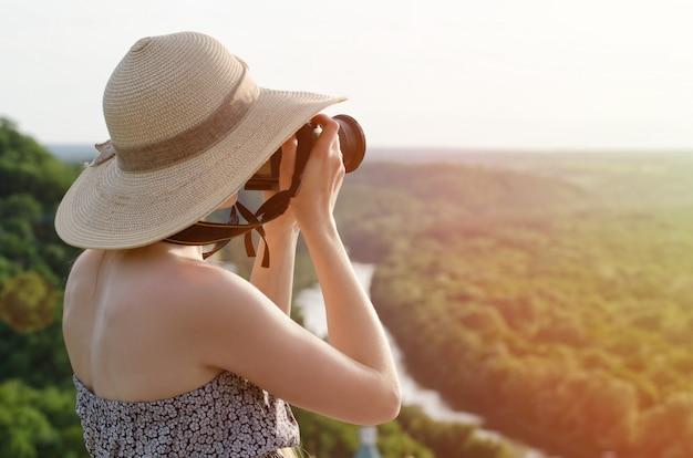 La ragazza prende le immagini contro della foresta e del fiume