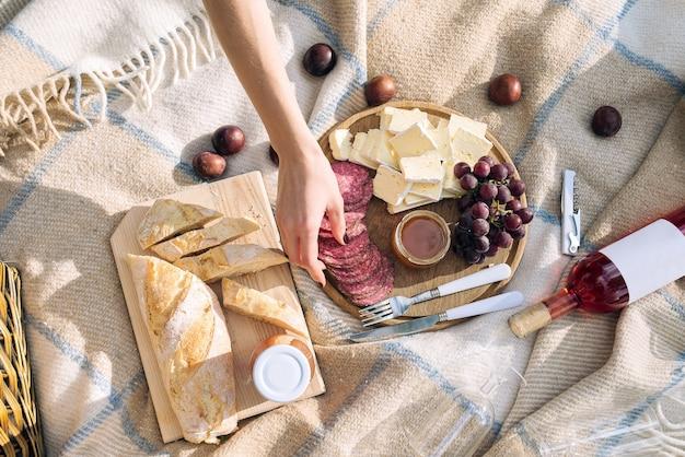 La ragazza prende il salame su un picnic. pranzo nella vista dall'alto del parco
