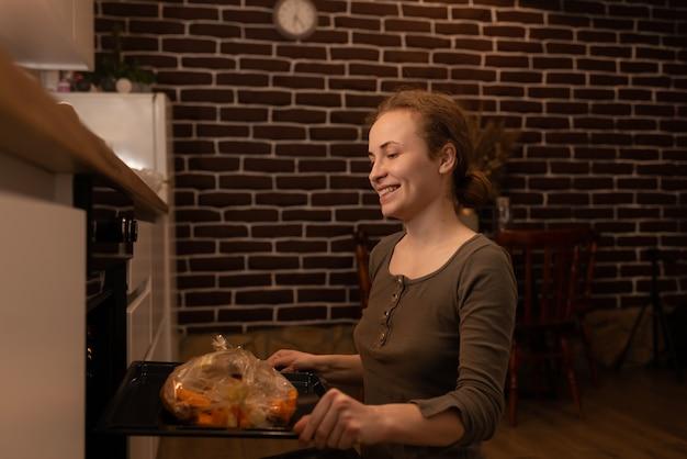 Ragazza che cattura pollo al forno dal forno. cuocere la carne a casa