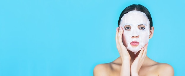 Ragazza che si prende cura della carnagione della pelle. cura della pelle e concetto di bellezza. maschera idratante. donna che applica la maschera sul viso, su sfondo blu. bella donna con maschera.