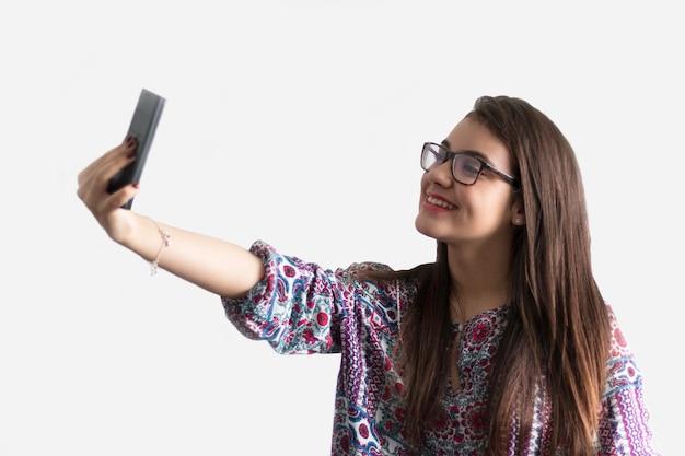Ragazza che prende selfie con sfondo bianco.