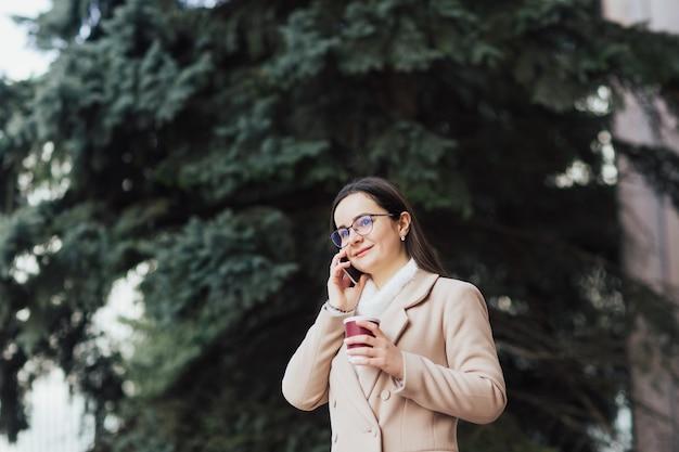 Ragazza parla su smartphone vicino a pino il giorno di primavera