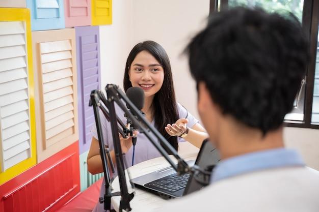 Una ragazza che parla e chiacchiera con un ragazzo davanti a un microfono durante un podcast