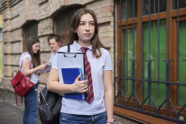 Studente di college dell'adolescente della ragazza che posa all'aperto in maglietta bianca con il legame. edificio in mattoni di sfondo, gruppo di studentesse. inizio delle lezioni, ritorno al college, copia spazio