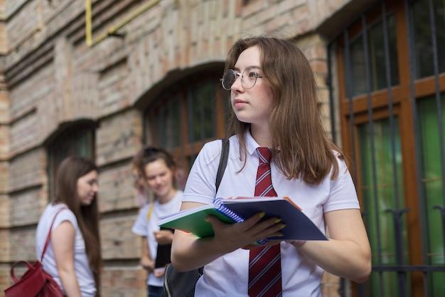 Studente di college dell'adolescente della ragazza che posa all'aperto in maglietta bianca con il legame in vetri. edificio in mattoni di sfondo, gruppo di studentesse. inizio delle lezioni, ritorno al college, copia spazio