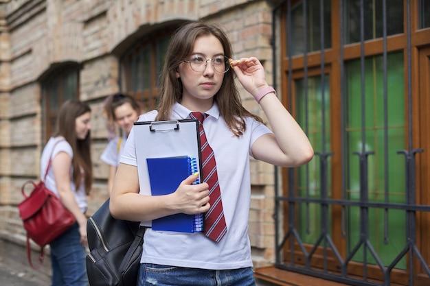 Studente di college dell'adolescente della ragazza che posa all'aperto in maglietta bianca con il legame in vetri. edificio in mattoni di sfondo, gruppo di studentesse. inizio delle lezioni, ritorno al college, copia spazio Foto Premium