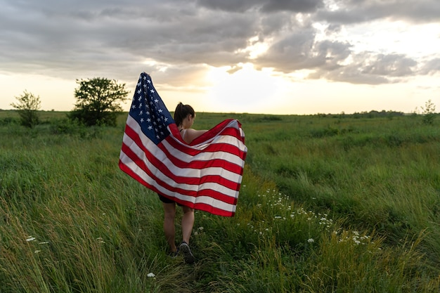 Ragazza adolescente femmina giovane donna in un campo avvolto nella bandiera degli stati uniti a stelle e strisce nel sole della sera.
