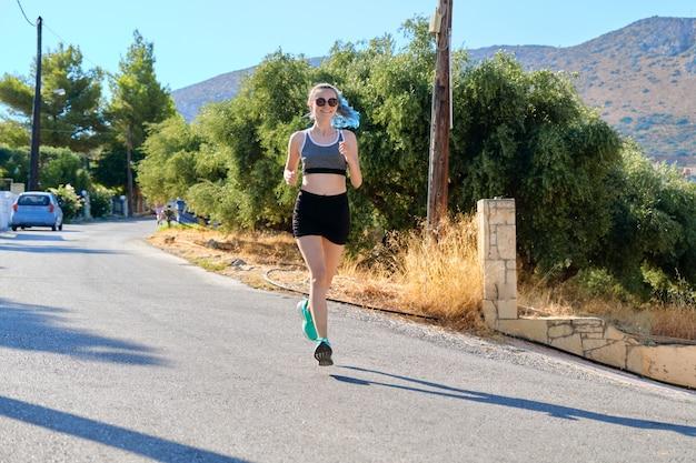 Corridore dell'adolescente della ragazza, corsa femminile sulla strada di montagna, stile di vita attivo degli adolescenti sani. esercizio all'aperto, bellissimo sfondo del paesaggio al tramonto