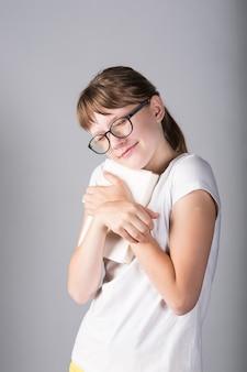 Ragazza adolescente con libro e con gli occhiali su sfondo grigio