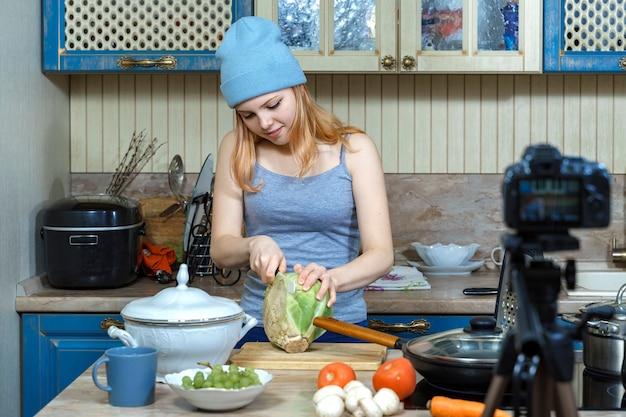 Ragazza adolescente giovane food blogger prepara il cibo, scrive la ricetta alla fotocamera.