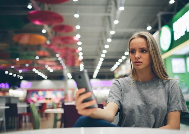 Ragazza che manda un sms sullo smartphone in un terrazzo del ristorante
