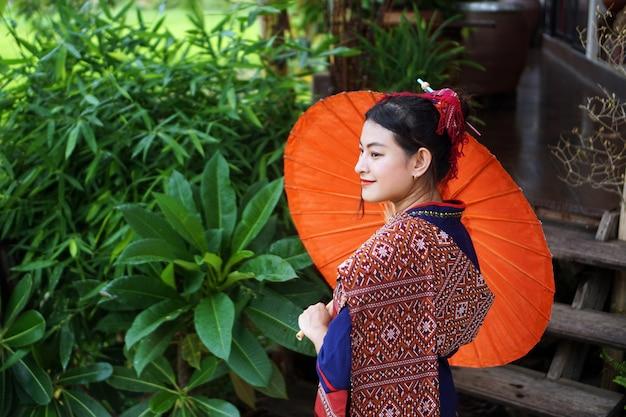 Ragazza in abito tradizionale tailandese con ombrello rosso nel giardino della casa in legno