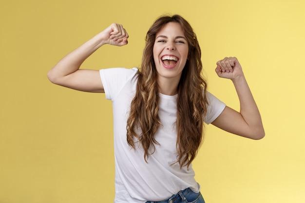 Ragazza grazie invito festa fantastica divertendosi scatenarsi alzando le mani rilassato sciolto ballando sincronizzazione labiale musica cool godendo momento indossare t-shirt bianca vestito casual celebrando sfondo giallo