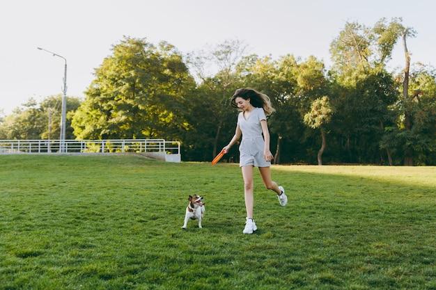 Ragazza che lancia il disco volante arancione al piccolo cane divertente, che lo cattura sull'erba verde. piccolo animale domestico di jack russel terrier che gioca all'aperto nel parco. cane e proprietario all'aria aperta.
