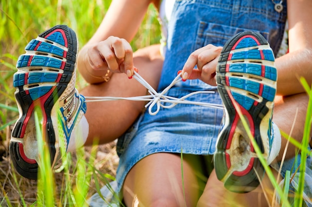 La ragazza lega i lacci delle scarpe da ginnastica al ragazzo