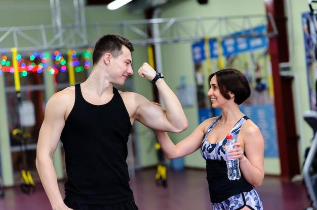 La ragazza tocca i muscoli di un ragazzo in palestra.