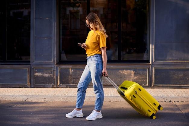 Turista della ragazza tiene il cellulare in mano, cammina per la città con la valigia gialla e guarda nel modo giusto