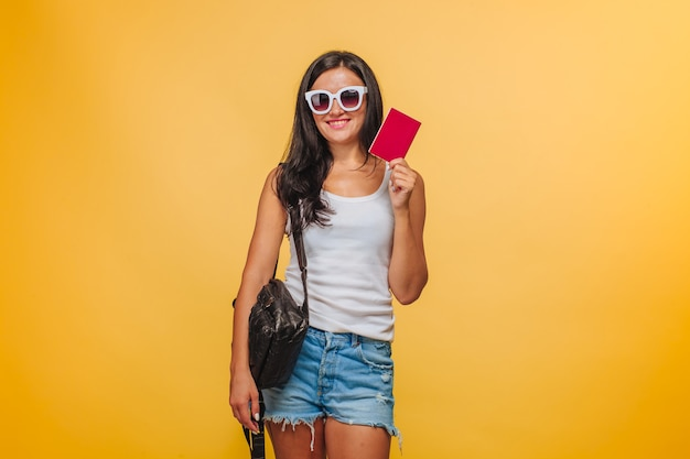 Turista della ragazza su uno sfondo giallo con uno zaino e un passaporto