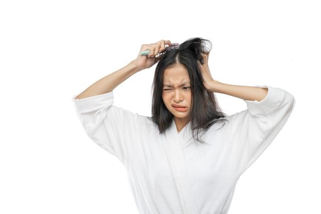 Una ragazza in un asciugamano che tiene un pettine con un'espressione infelice