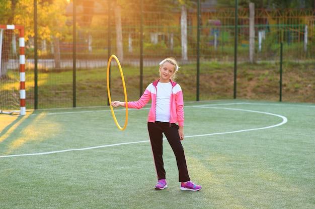 Ragazza in una tuta da ginnastica con un cerchio tra le mani nel parco giochi.