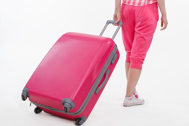 Viaggiatore della ragazza con la valigia rosa. borsa da viaggio rosa e ragazza che la tiene. foto di una ragazza di spalle. ragazza prendendo borsa da viaggio rosa su sfondo bianco.