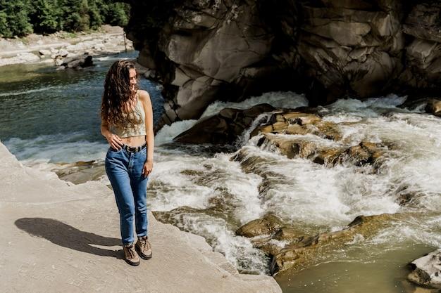 Ragazza in viaggio nelle montagne di karpathian e sensazione di libertà. cascata nel fiume di montagna.