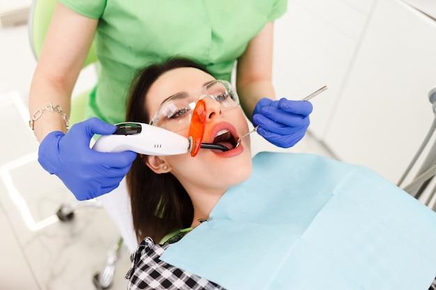 La ragazza tratta i denti in odontoiatria. dentista che usando la lampada uv di cura dentale sui denti del paziente