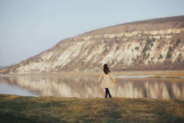 Ragazza in trench che cammina sulla riva del fiume
