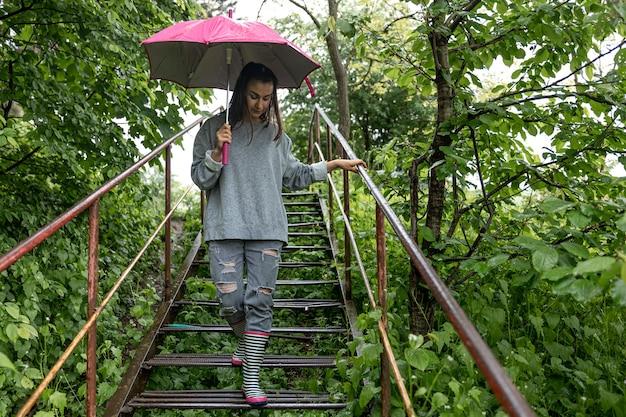 Ragazza sotto un ombrello durante una passeggiata nella foresta primaverile sotto la pioggia