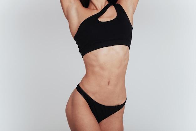La ragazza in biancheria intima con la figura snella mostra il suo corpo al muro bianco.