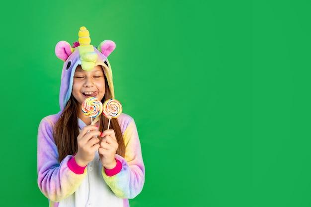 Ragazza in costume da unicorno che mangia lecca-lecca