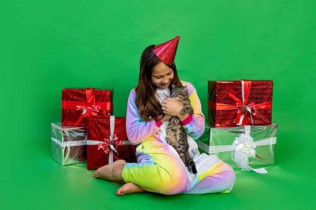 Ragazza in costume da unicorno con scatole regalo e gioca con il gatto