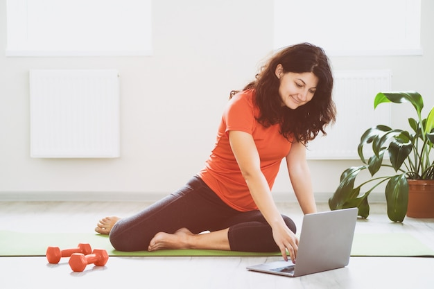 Una ragazza usa un laptop durante un allenamento online - una ragazza fa un allenamento a casa in una stanza