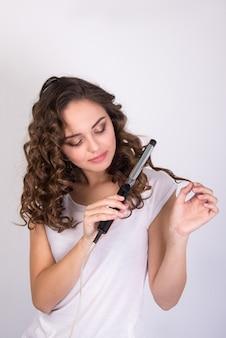 Ragazza che utilizza l'arricciacapelli che fa l'acconciatura facile moderna su fondo bianco