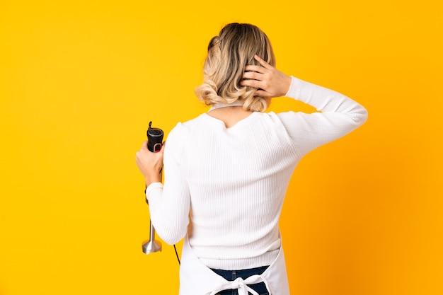 Ragazza che per mezzo del frullatore a immersione isolato sulla parete gialla nella posizione posteriore e pensare