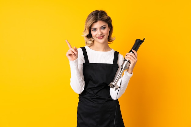 Ragazza che utilizza il frullatore a immersione isolato sulla parete gialla che mostra e solleva un dito in segno del meglio