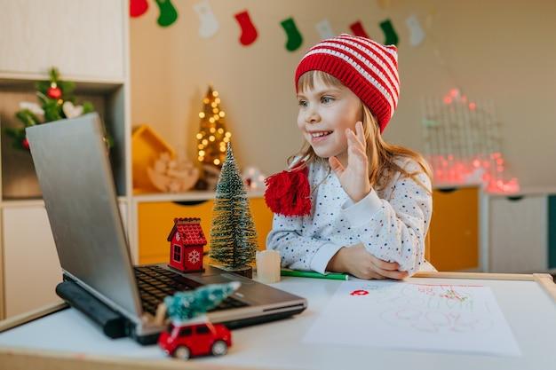 Ragazza che utilizza computer portatile per la videochiamata nella stanza dei bambini nel periodo natalizio
