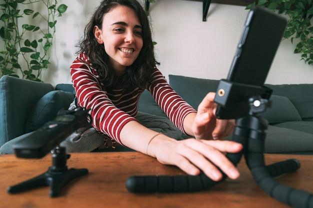 Ragazza che usa il telefono per registrarsi da casa messa a fuoco selettiva sulla ragazza concetto di video blogging