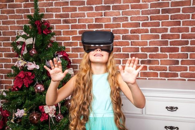 Ragazza che utilizza le cuffie per realtà virtuale durante le vacanze di capodanno e divertiti.