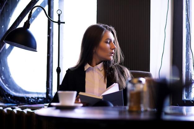 Una ragazza in un caffè vintage siede vicino alla finestra