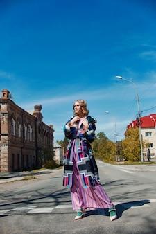 Ragazza in un abito fatto a mano di moda etnica vintage in posa all'aperto. insolito costume retrò sul corpo della ragazza, sorriso ed emozioni allegre. russia, sverdlovsk, 10 giugno 2019