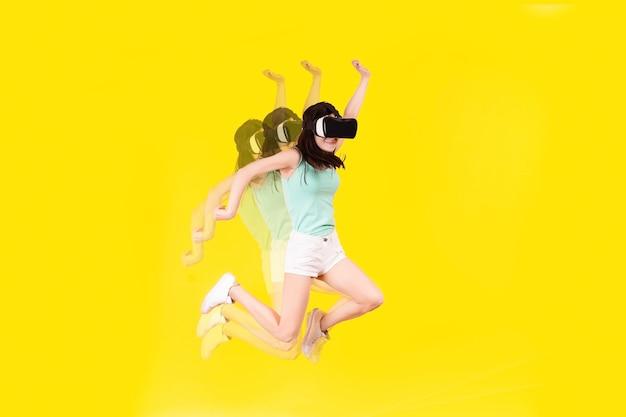 La ragazza con gli occhiali vr della realtà virtuale sta saltando su uno sfondo giallo