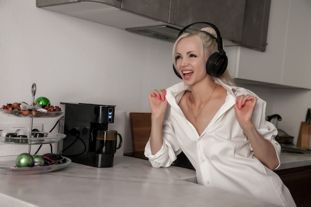 Ragazza in attesa che venga preparato il caffè nella macchina del caffè e ascolta la musica. processo di preparazione del caffè a casa. carina donna slava in cucina a casa. emozioni al femminile. concetto di comfort domestico. spazio per il testo