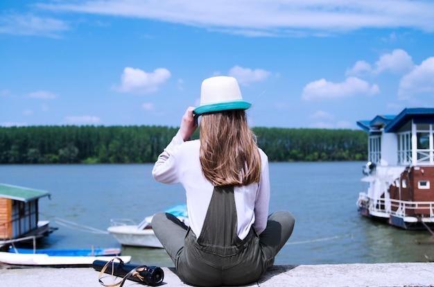 Ragazza che aspetta l'estate dal fiume. ragazza indietro che si siede sulla riva del fiume e che osserva sull'isola della foresta nell'acqua blu.