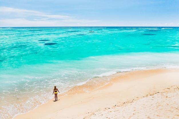 Ragazza che cammina lungo la spiaggia con turisti provenienti da tutto il mondo che visitano l'isola paradisiaca di mauritius.