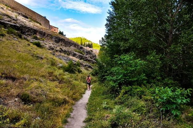 Una ragazza che cammina lungo uno stretto sentiero attraverso la foresta