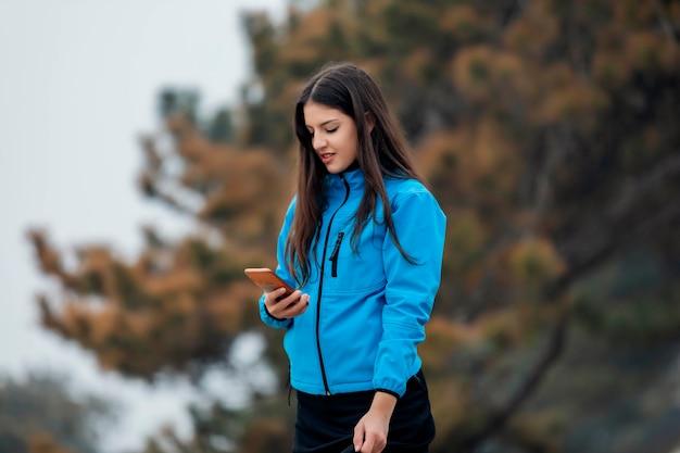 Ragazza che cammina e che manda un sms sullo smart phone nella via