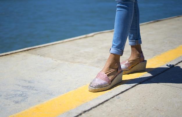 Ragazza che cammina su una linea di attenzione gialla vicino a un molo